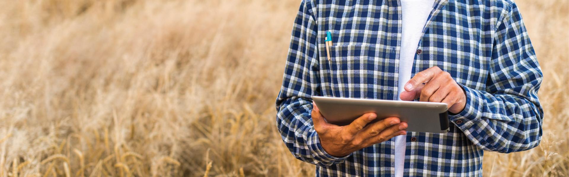 man in field using tablet
